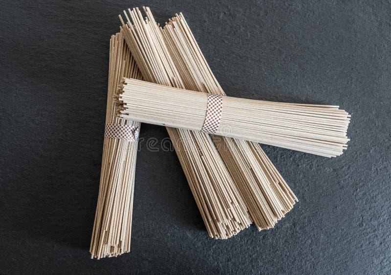 Tagliatelle giapponesi crude secche di soba fatte di grano saraceno sul tagliere dell'ardesia fotografia stock