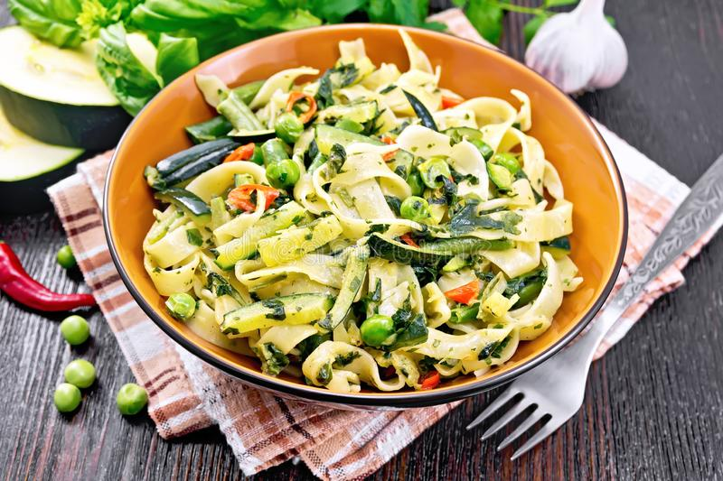 Tagliatelle with green vegetables on wooden board stock photography