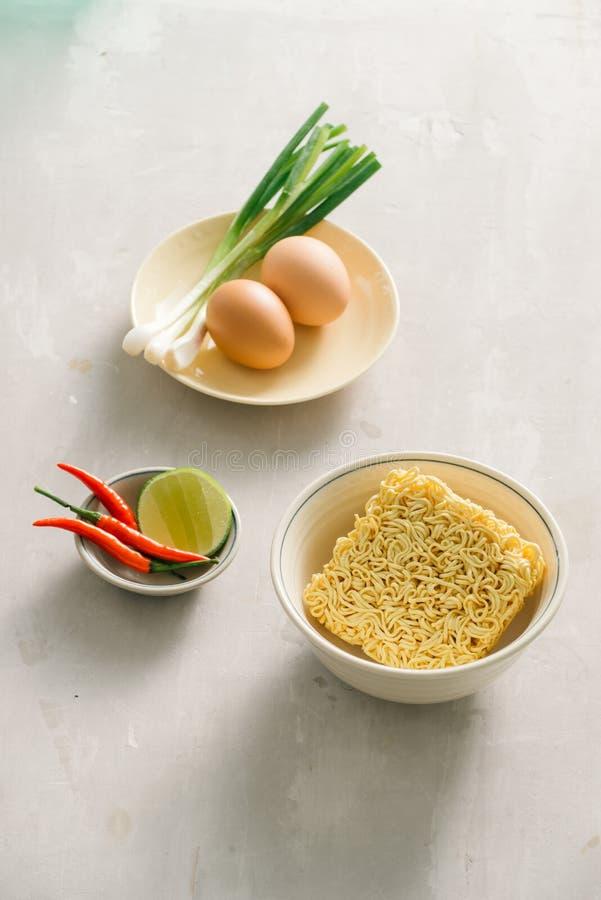Tagliatelle istantanee in ciotola e piatti laterali vegetali su fondo di pietra Concetto rapido & facile dell'alimento fotografia stock libera da diritti