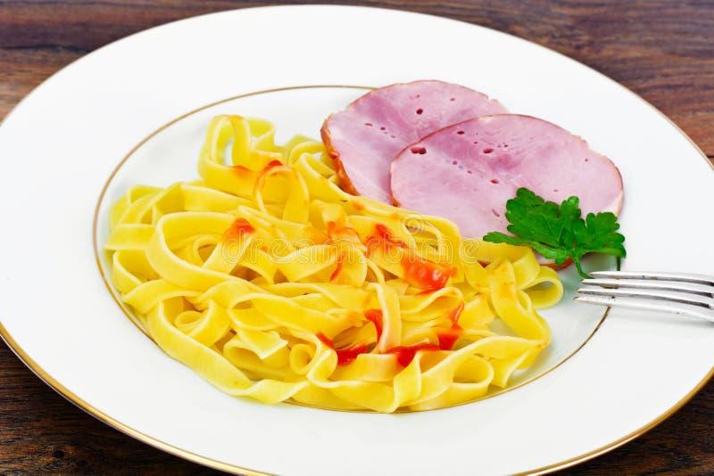 Tagliatelle italiane, pasta con la salsiccia, salame e ketchup immagine stock
