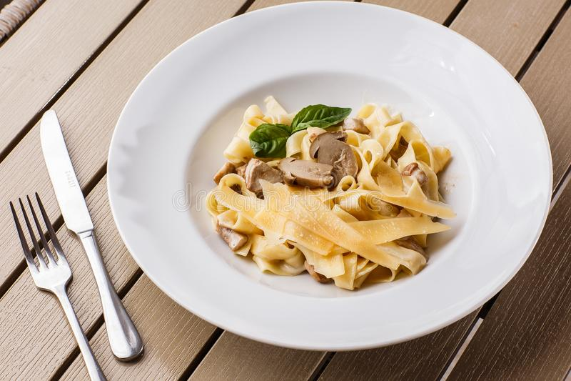 Tagliatelle makaronu jarski naczynie z pieczarkami dekorował z basilem Wyśmienicie lunch z makaronu i bielu pieczarkami zdjęcie stock