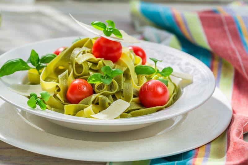 Tagliatelle med tomaten och basilika i det soliga köket royaltyfri foto