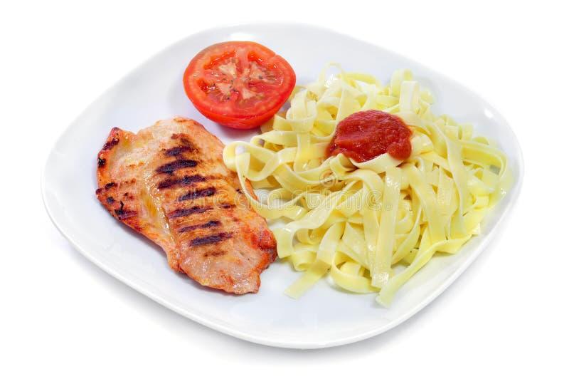 Tagliatelle med tomatsås och grillad höna arkivfoto