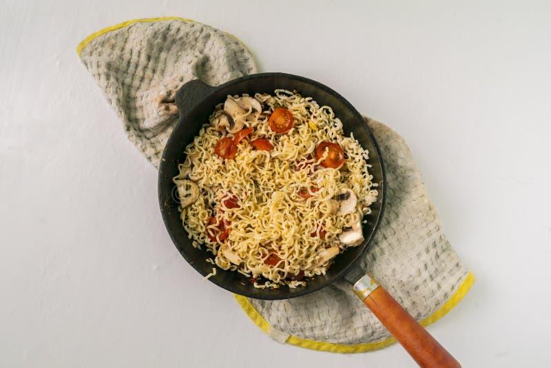 tagliatelle nella pentola con i pomodori ciliegia del aand dei funghi, cookings italiani della pasta fotografia stock libera da diritti