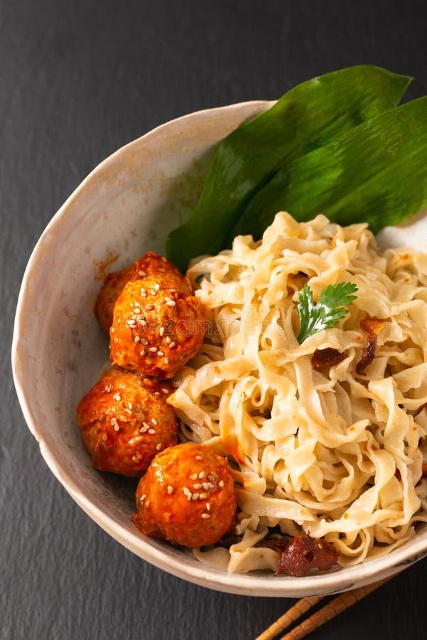 Tagliatelle orientali casalinghe dell'uovo di concetto asiatico dell'alimento e polpette piccanti in ciotola ceramica su fondo ne immagine stock