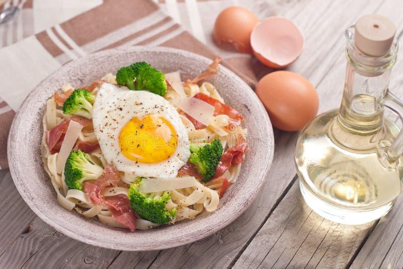 Tagliatelle pasta with broccoli, prosciutto and fried egg. Tagliatelle pasta with broccoli, prosciutto and fried egg stock photos