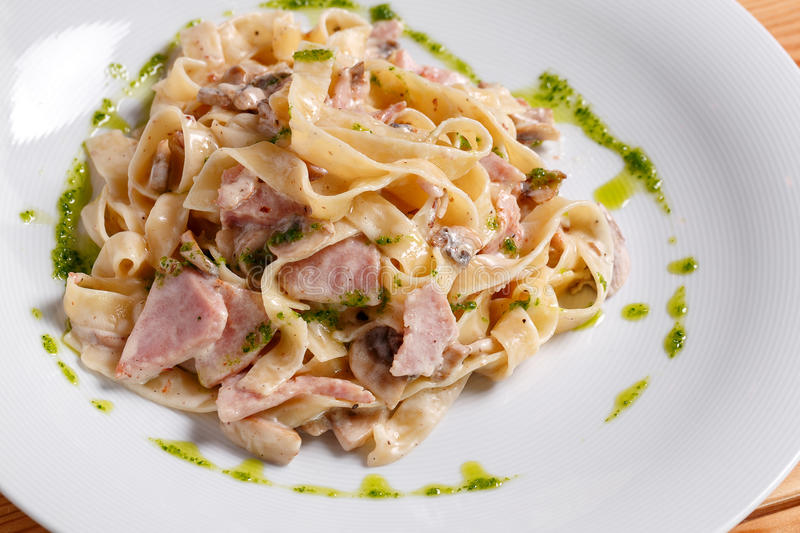 Tagliatelle pasta with ham, mushrooms and yolk. Selective focus stock images