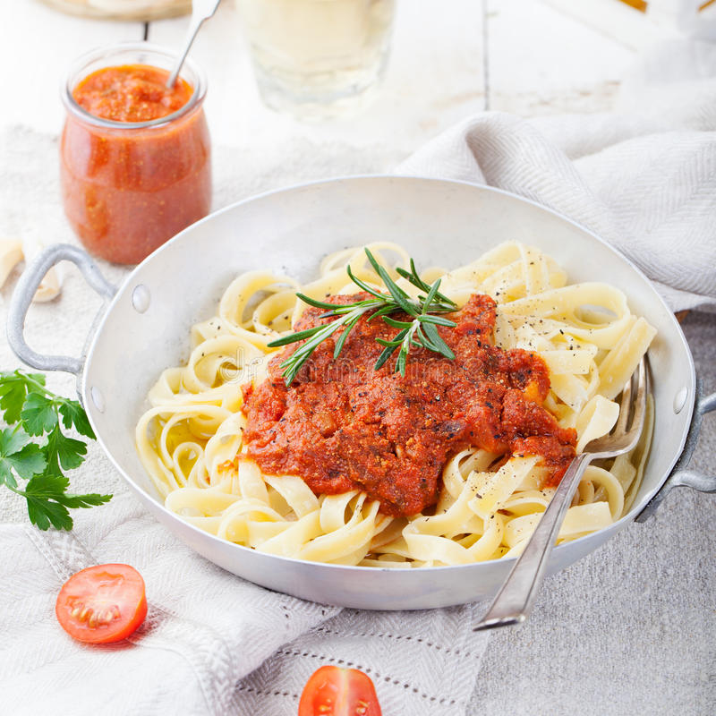 Tagliatelle pasta with tomato sauce and red pesto Italian cuisine. Top view royalty free stock photography