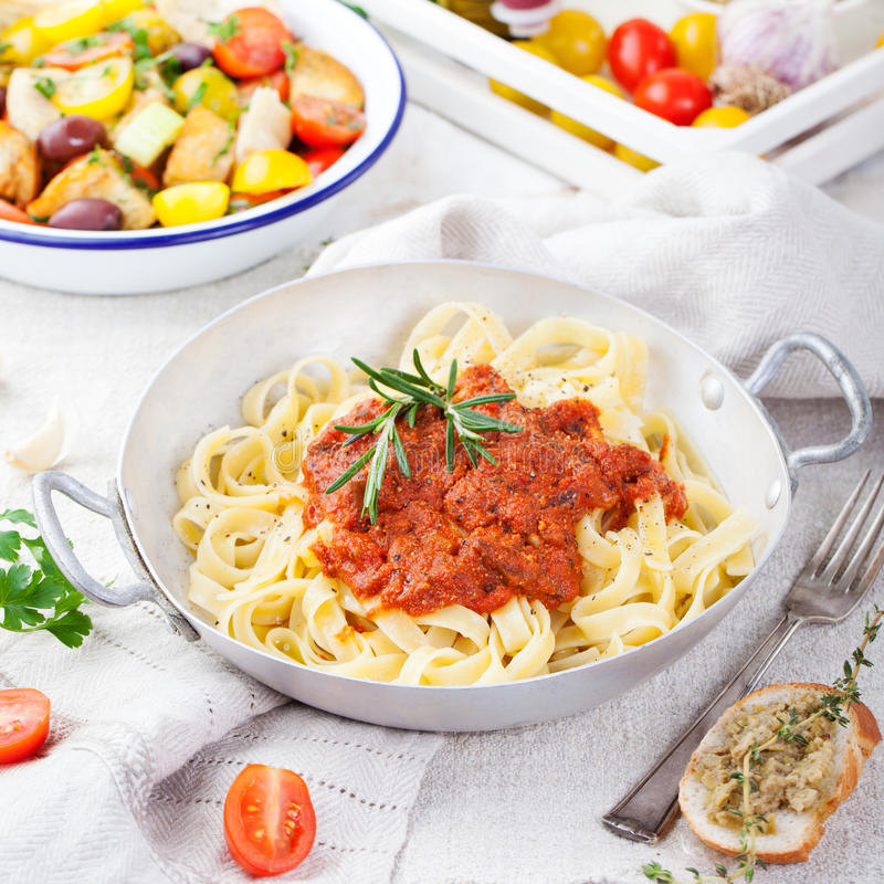 Tagliatelle pasta with tomato sauce and red pesto Italian cuisine. Top view stock photos