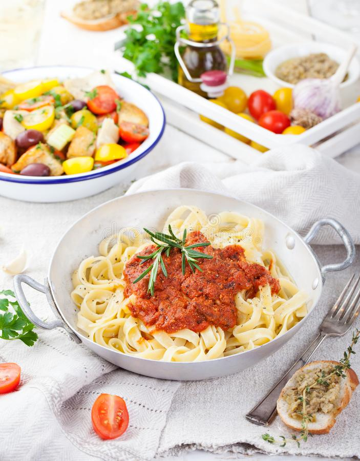 Tagliatelle pasta with tomato sauce. And red pesto Italian cuisine Top view royalty free stock images
