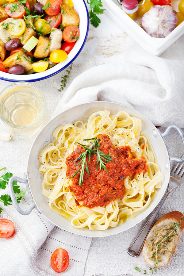 Tagliatelle pasta with tomato sauce and red pesto Top view. Tagliatelle pasta with tomato sauce and red pesto Italian cuisine Top view stock image