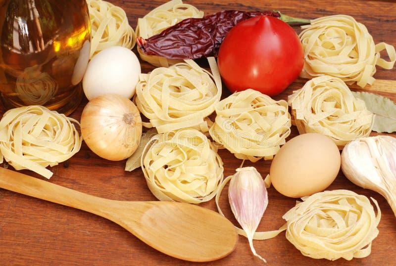 Tagliatelle pastaingredienser på träbräde royaltyfria bilder