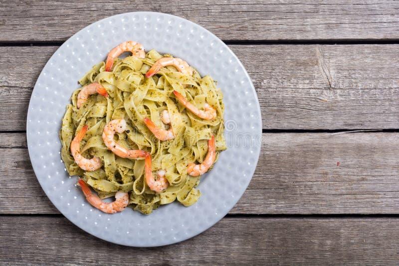 面团tagliatelle有调味汁pesto和虾意大利料理背景 库存图片