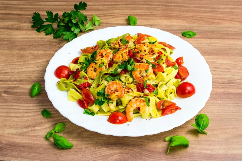 Tagliatelle with shrimps and tomatos stock photos