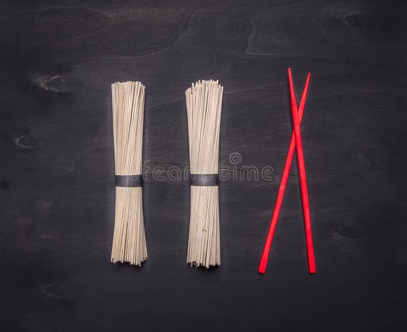 Tagliatelle tradizionali di soba del grano saraceno con i bastoncini rossi presentati in una fila sulla fine rustica di legno di  fotografia stock libera da diritti