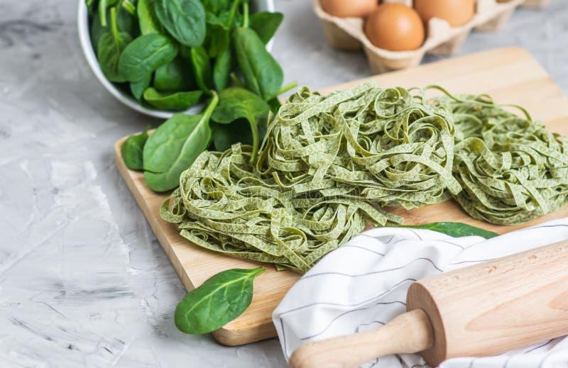 Tagliatelle verdi casalinghe crude italiane della pasta degli spinaci della preparazione che cucinano gli ingredienti differenti  fotografie stock
