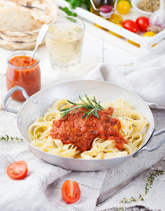 Tagliatellepasta med tomatsås och röd pestoitalienarekokkonst royaltyfria bilder