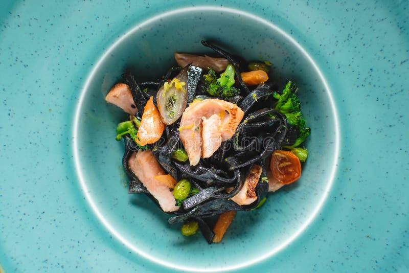 Tagliatelles noires de pâtes avec des saumons et des légumes image libre de droits