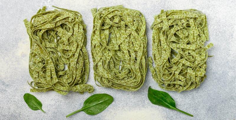Tagliatelles vertes italiennes faites maison crues d'épinards de pâtes étroitement  Nouilles sèches Fond culinaire photographie stock