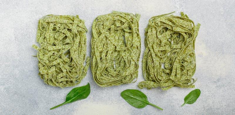 Tagliatelles vertes italiennes faites maison crues d'épinards de pâtes Nouilles sèches photographie stock libre de droits