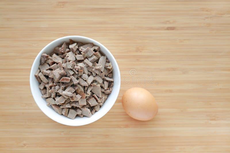 Tagliato del fegato bollito della carne di maiale in ciotole bianche sul bordo di legno con l'uovo fotografia stock