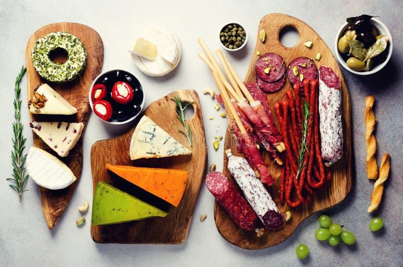 Tagliere con carne affumicata fredda, prosciutto di Parma, salame, assortimento dei formaggi, grissini, capperi, olive su grey fotografie stock libere da diritti