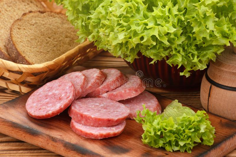 Tagliere con la salsiccia affumicata affettata per i panini fotografia stock libera da diritti