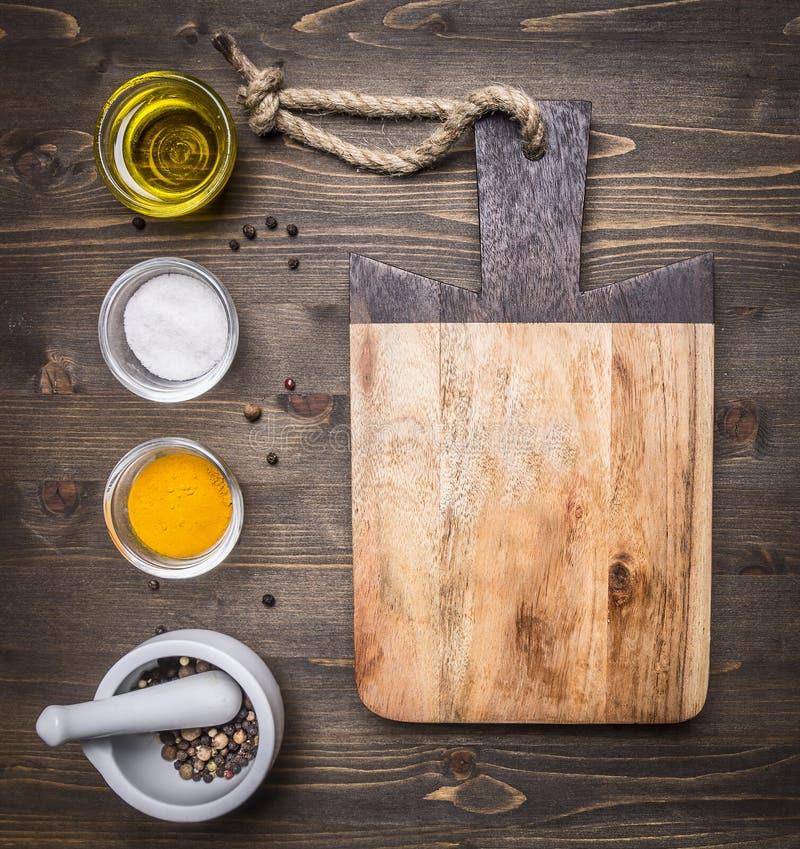 Tagliere con petrolio, sale e pepe con la fine rustica di legno di vista superiore del fondo del mortaio su immagine stock