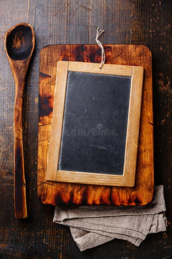 Tagliere, cucchiaio di legno e bordo di gesso fotografia stock libera da diritti