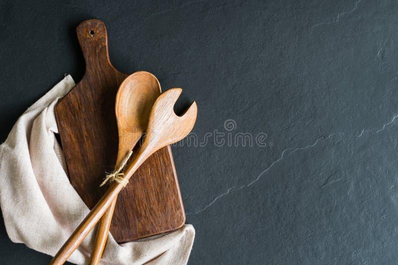 Tagliere di legno anziano su fondo di pietra nero fotografie stock