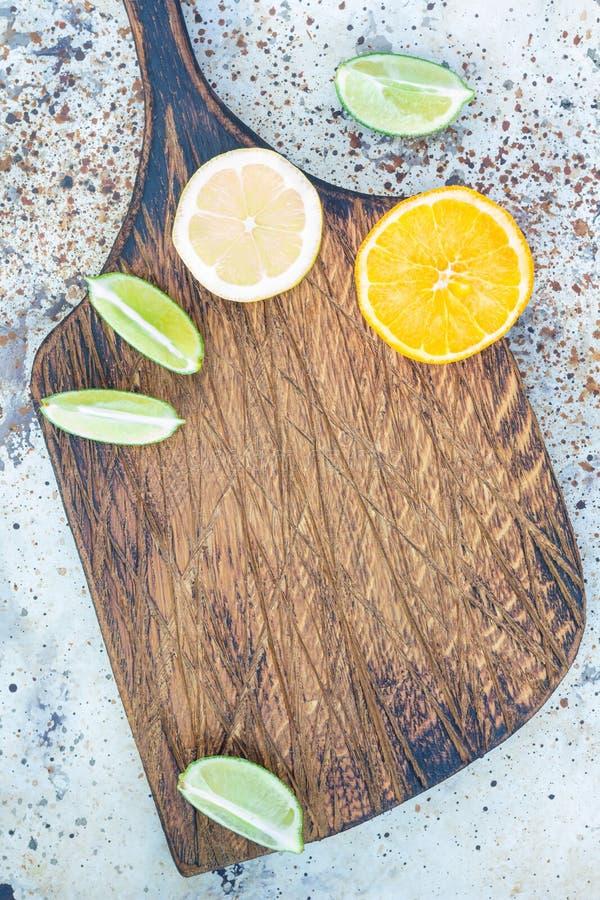 Tagliere di legno con l'agrume su fondo concreto, spazio della copia immagine stock