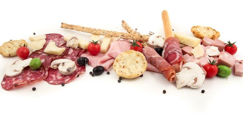 Tagliere di legno con vario salame italiano su fondo bianco immagine stock