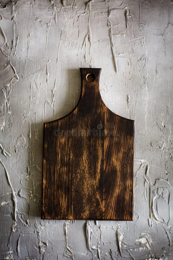Tagliere di legno su un fondo concreto fotografia stock