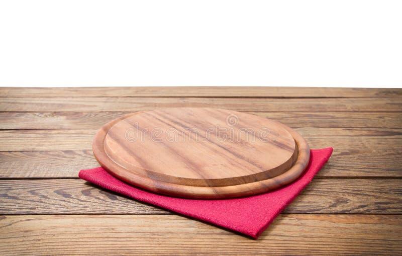 Tagliere rotondo dell'alimento della pizza e tovagliolo rosso della tovaglia sulla tavola di legno marrone isolata su fondo bianc immagini stock libere da diritti