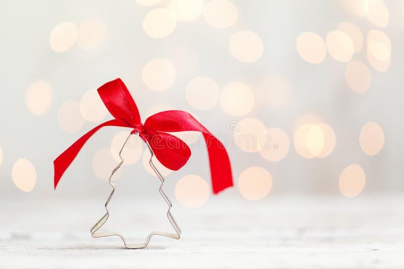 Taglierina del biscotto dell'albero di Natale con l'arco rosso su fondo bianco con lo spazio della copia Concetto di Natale immagini stock