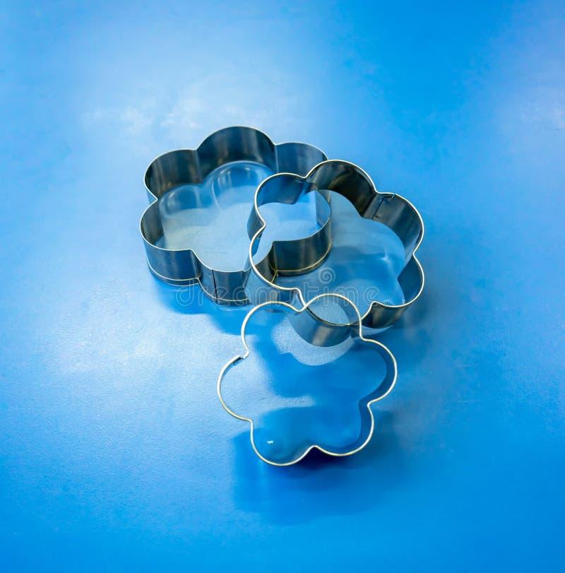 Taglierina del biscotto del fiore isolata sulla tavola blu immagine stock libera da diritti