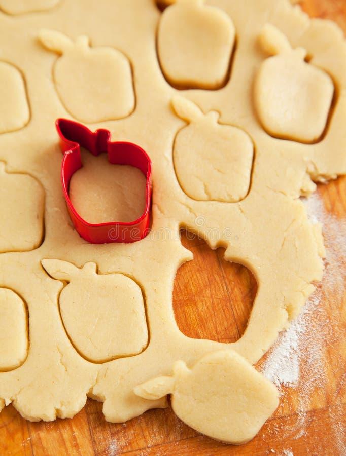 Taglierina a forma di mela del biscotto sulla pasta cruda del biscotto immagine stock libera da diritti