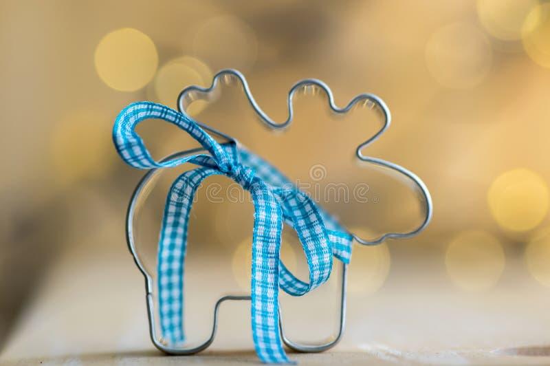 Taglierina metallica della renna di Natale con l'arco blu alle luci di Natale magiche su fondo fotografia stock libera da diritti