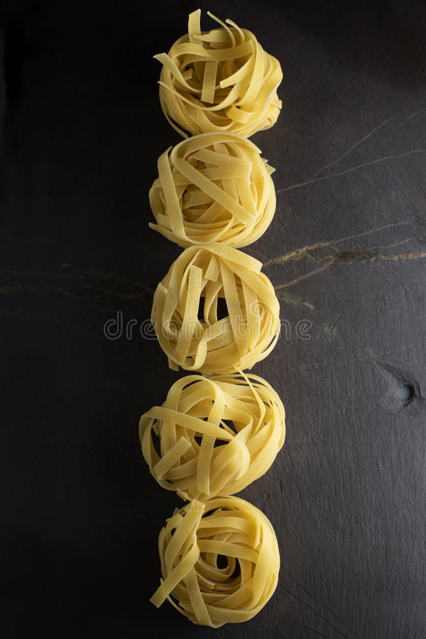 Taglietelle. Uncooked tagletelle on a dark slate background in a row side lit, copy space, vertical or horizontal orientation stock photo