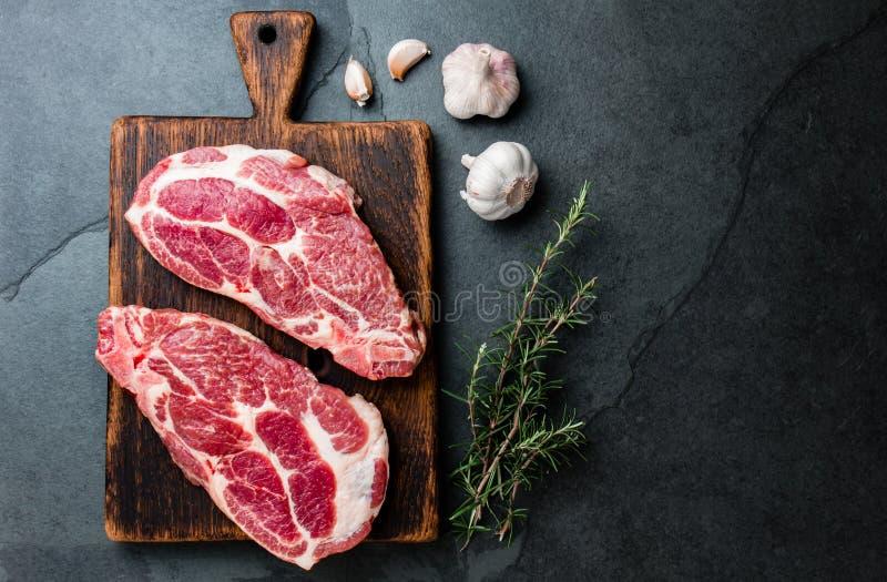 Taglio crudo della cotoletta della carne di maiale per il BBQ della griglia con le erbe sul bordo di legno, fondo dell'ardesia, v fotografia stock