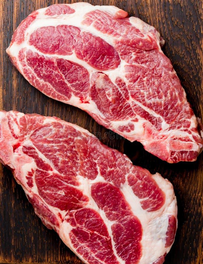 Taglio crudo della cotoletta della carne di maiale per il BBQ della griglia con le erbe sul bordo di legno, fondo dell'ardesia, v immagini stock libere da diritti