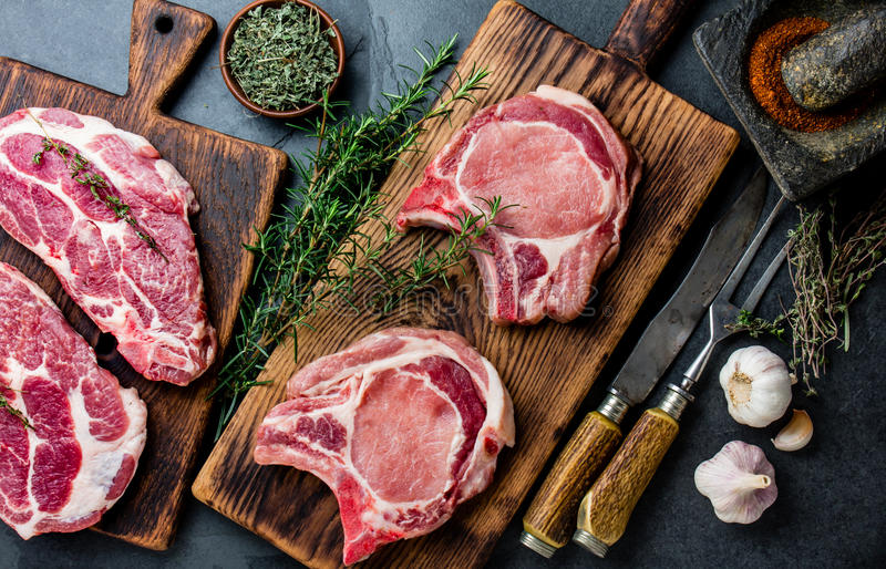 Taglio crudo della cotoletta della carne di maiale per la frittura sulla griglia e sulla pentola con le erbe, aglio sui bordi di  fotografie stock libere da diritti