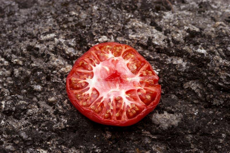 Taglio del pomodoro a metà che si trova sulla pietra nera fotografia stock libera da diritti