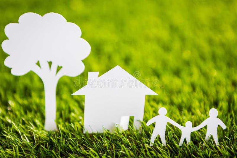 Taglio della carta della famiglia con la casa e dell'albero su erba immagine stock libera da diritti