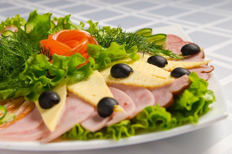 Taglio di banchetto con il prosciutto, le squisitezze della carne, il formaggio, la salsiccia fumata, l'oliva, la lattuga ed il p immagine stock