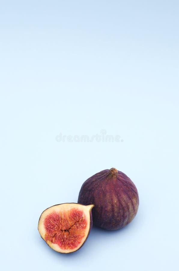Taglio e tutto dei fichi della frutta fresca su un fondo blu immagini stock libere da diritti