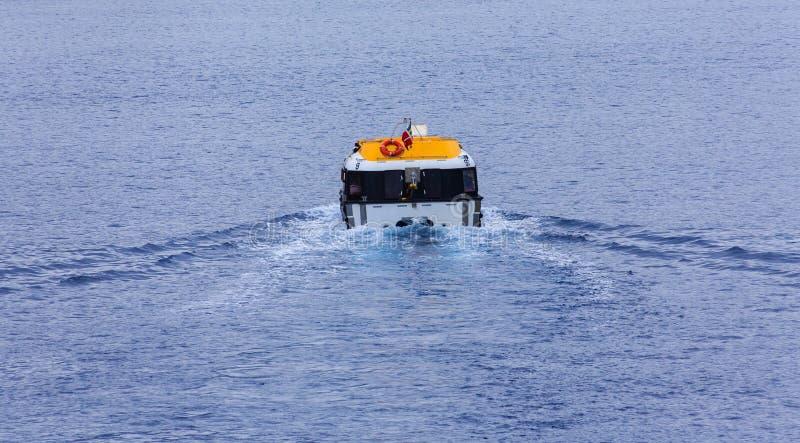Taglio giallo e bianco della lancia di salvataggio attraverso l'acqua blu fotografia stock libera da diritti