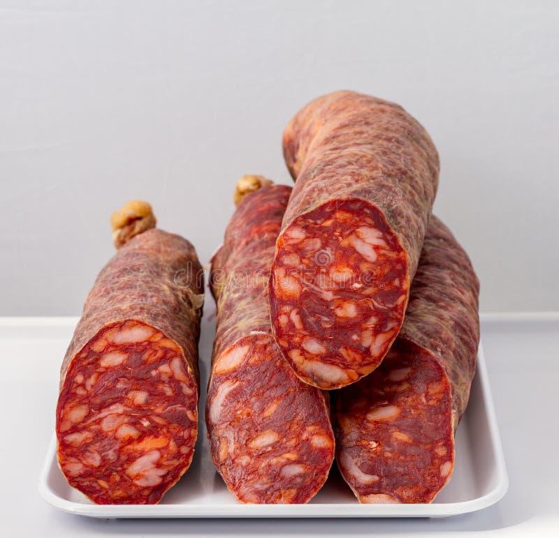 Taglio iberico della salsiccia a metà su fondo bianco fotografie stock libere da diritti