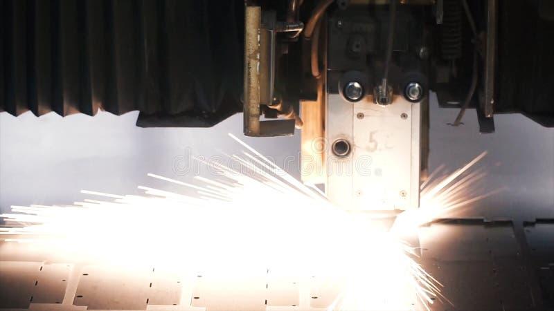Taglio a macchina del laser della lamiera sottile clip Le scintille volano dal laser da CNC tagliente automatico, macchina dello  fotografia stock libera da diritti