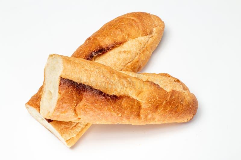 Taglio a metà, pane delle baguette, pane francese, baguette organiche delle baguette francese su bianco fotografie stock